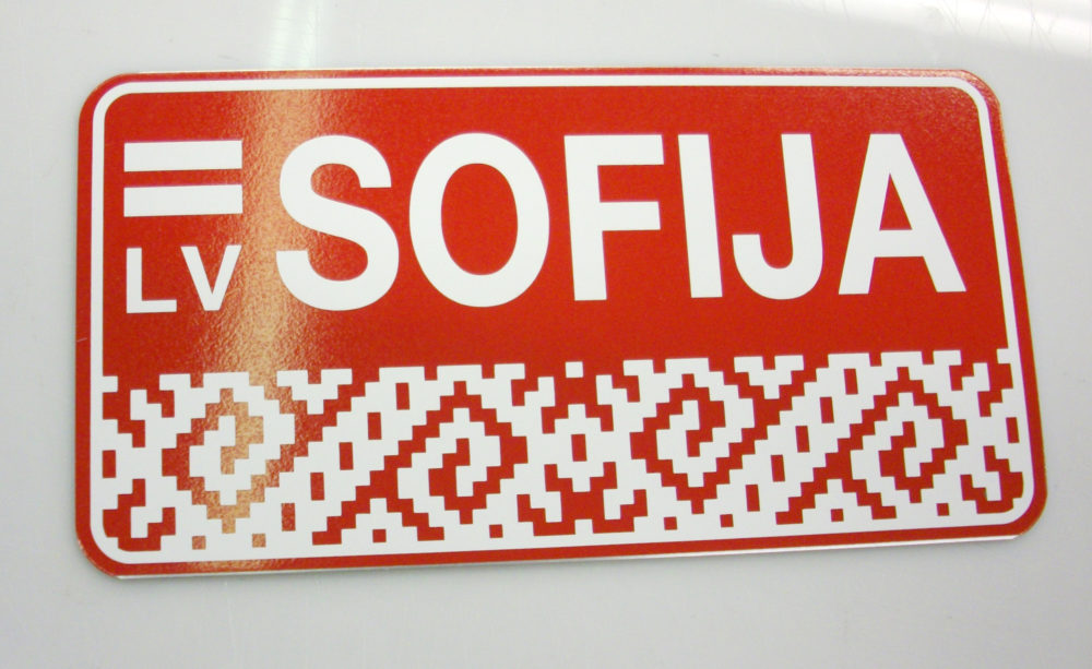 LATSIGN Informatīvā ratiņu vārda numura zīme uz sarkana fona ar latvju rakstiem Latvijas karogu- Sofija