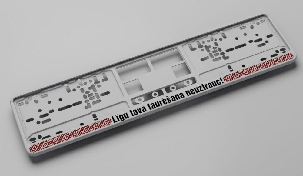 LATSIGN Auto numura turētājs baltā krāsā ar latvju rakstiem sarkanā krāsā un melnu uzrakstu - Līgu tava taurēšana neuztrauc!