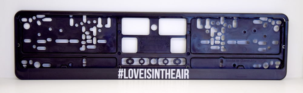 LATSIGN Auto numura turētājs ar uzrakstu - Love Is In The Air